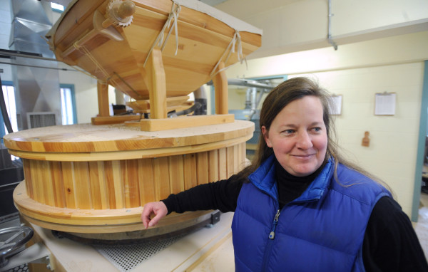 Amber Lambke, president of Maine Grains grist mill, is shown with the Austrian-made stone mill used to mill grains at the Skowhegan facility.