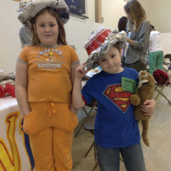 Children model hats they created from recycled newspaper with the guidance of Windover Arts Center at the HOPE Festival.