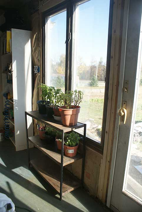 Plants sit in the sunlight in front of a &quotwall of glass&quot in Jj Starwalker's living room on Fussing Duck Farm in Corinth. A sliding glass door and two large windows -- all found for free -- were installed for passive solar heating and to help start seedlings.