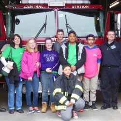 JMG students network with local businesses. Here they pose with members of Portland Fire Department.
