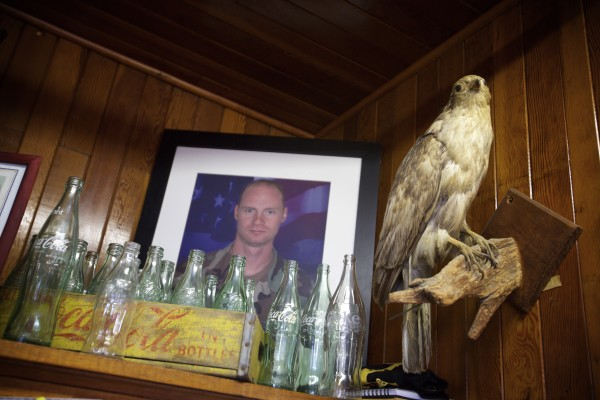 A photo of Michael Severance, a man slain by his wife in Texas, rests on a shelf near a taxidermied raptor at the Pine Tree Store in Grand Lake Stream which is now under the ownership of his father, Leslie Severance, and Brinda Leighton at the popular fishing destination in Maine.