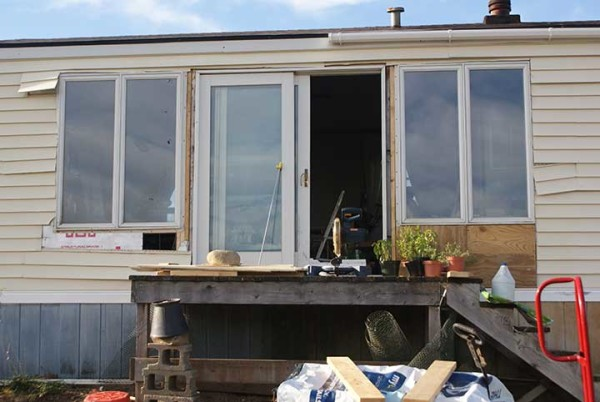 New windows and a sliding glass door were installed at the home on Fussing Duck Farm to allow more passive solar heating and to help start seedlings.