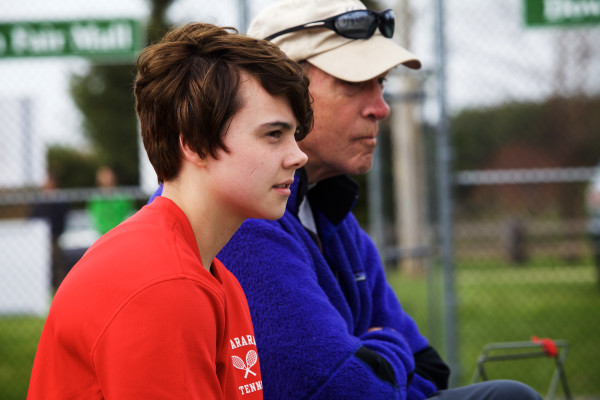 Transgender athlete Leo Eichfeld, 14, watches a match with Mt. Ararat High School tennis coach Dan Foley. Eichfeld came out this year when he joined the swim team.