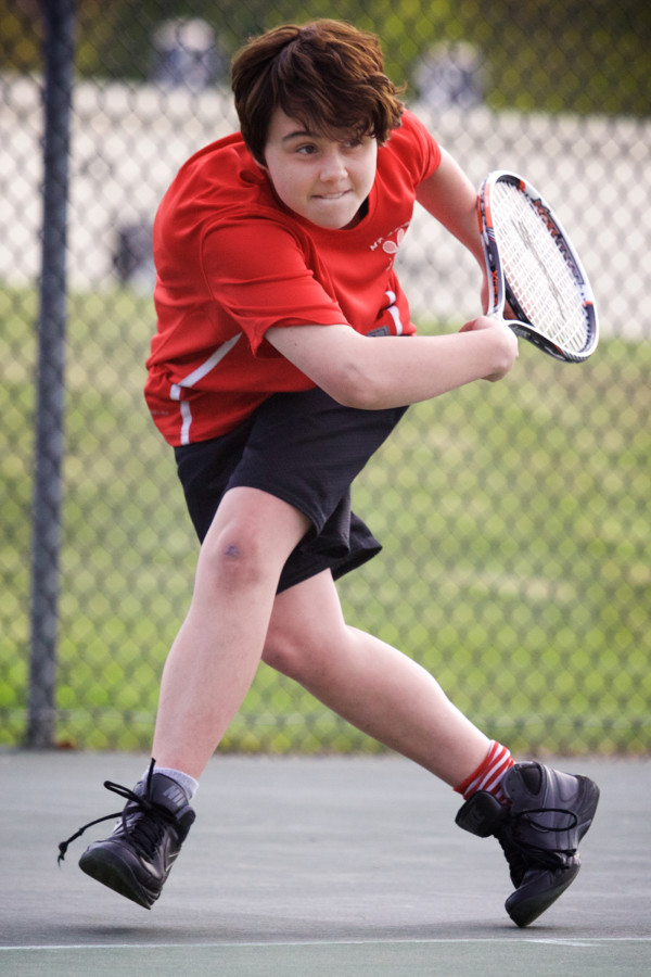 Transgender athlete Leo Eichfeld, 14, returns a volley during a match against arch-rivals Brunswick High School. Eichfeld came out this year when he joined the swim team.
