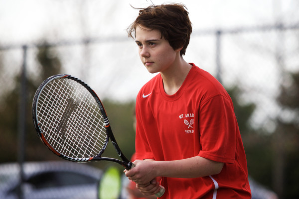 Transgender athlete Leo Eichfeld, 14, gets ready to return a serve during a match against arch-rivals Brunswick High School. Eichfeld came out this year when he joined the swim team.