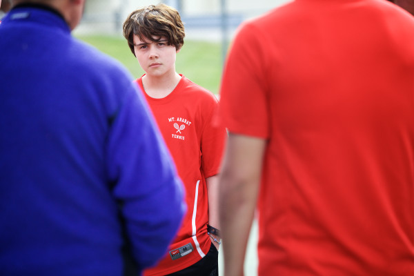 Transgender athlete Leo Eichfeld, 14, listens to Mt. Ararat High School tennis coach Dan Foley before a match against arch-rivals Brunswick High School. Eichfeld came out this year when he joined the swim team.
