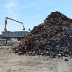 Waste sits in piles at ecomaine's southern Maine landfill while a magnet on a crane pulls metals from the processed refuse in the background. The Maine facility is the first landfill in North America where metal is being successfully mined.