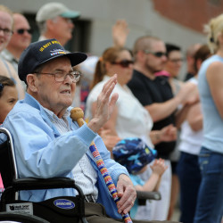 World War II veteran Linwood Carroll, 92, of Greenbush waves as veterans walk by in Bangor's Memorial Day parade Monday. Carol served in the U.S. Navy from 1943-1946.