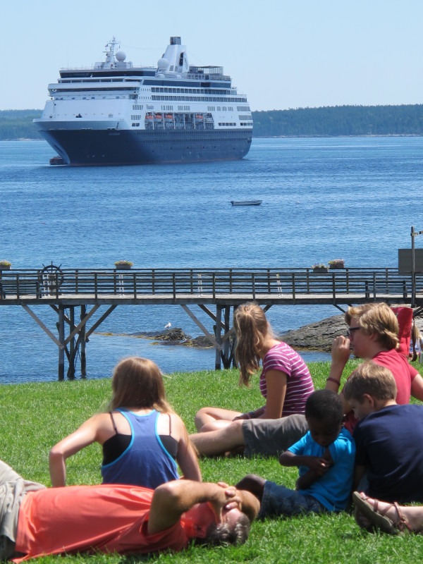 Tourists relax in Agamont Park in Bar Harbor while the cruise ship Maasdam sits anchored offshore in Frenchman Bay in this August 2013 file photo.