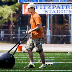 Caleb Johnson, a subcontractor of Northeast Turf of South Portland, smoothes freshly laid artificial turf at Fitzpatrick Stadium in Portland on Thursday, May 7.