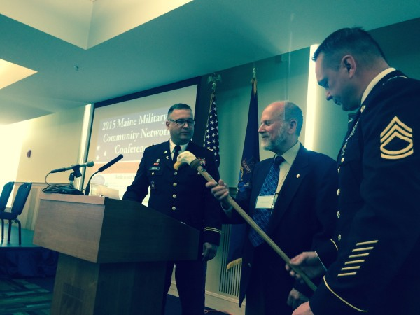 Col. Andrew Gibson (left), a Maine Army National Guard chaplain, and Sgt. 1st Class Nathaniel Grace (right), community liaison for the Maine Military Community Network, hands a Maine veteran-made cane to Dr. Jonathan Shaw, a Department of Veterans Affairs psychologist who specializes in combat trauma, on Wednesday in Orono.