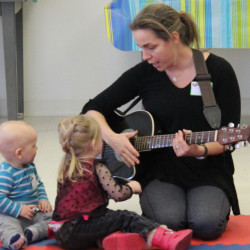 Two fascinated children get an up-close look at Jess Day and her guitar during a recent Music Together playgroup.