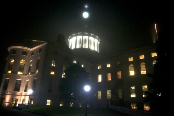 The State House shines through the the fog Tuesday night.