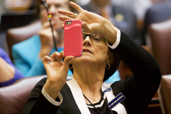 Anne-Marie Mastraccio, D-Sanford, takes a picture of the lighted vote tally board early Wednesday morning as the legislature passes a two-year budget.