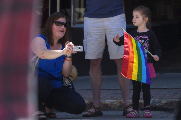 Elena Domina (right), 4, waves to people in the parade with Angela Domina during the annual Bangor Pride Festival through downtown Bangor on Saturday.