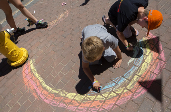 Emerson Merrill-Maguire (left) and Owen Connor-Self, both 9, draw a rainbow with chalk on the sidewalk during the annual Bangor Pride Festival through downtown Bangor on Saturday.
