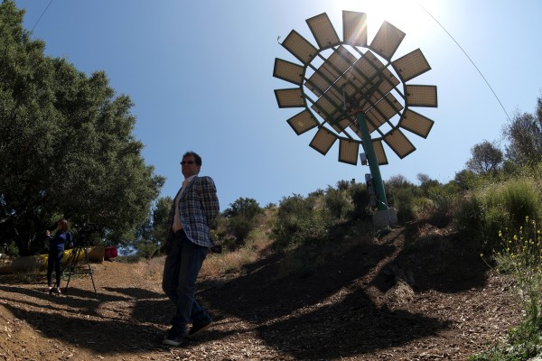 A man walks past a solar Sun Flower designed by filmmaker James Cameron at MUSE School in Malibu, California May 19, 2015. Designed as functional art pieces, using existing photovoltaic technologies, the Sun Flowers produce between 75 percent and 90 percent of the campus' power depending upon available daylight.