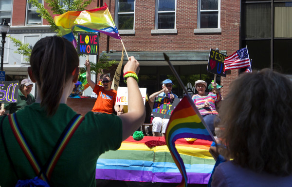 People wave pride flags during the annual Bangor Pride Festival through downtown Bangor on Saturday.