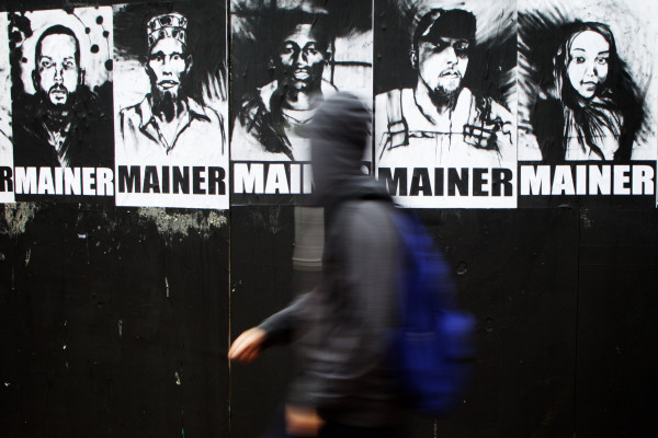 A pedestrian looks at a new art installation on a boarded up storefront on Tuesday in Portland. The posters made from original charcoal drawings are the work of Orson Horchler, sometimes known as Pigeon.