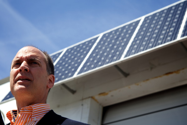 Real estate developer Tim Soley speaks at a electric car event in Portland in this 2014 file photo below a set of solar panels. Soley owns a parking garage on Fore Street equipped with panels and had a pair of electric car charging stations installed there.