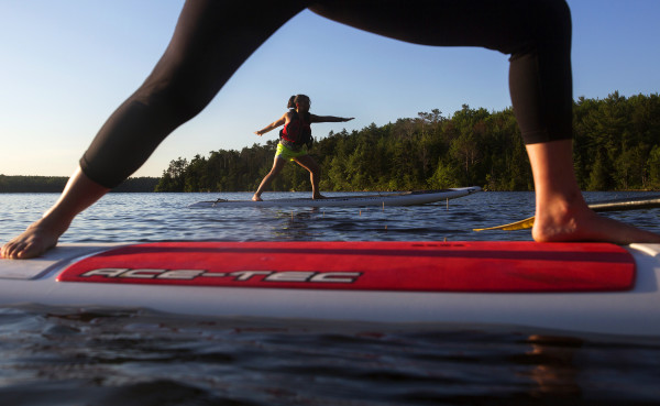 Emma Mattingly, 9, does the warrior pose during an Acadia Stand Up Paddle Boarding yoga class at Echo Lake on Mount Desert Island.