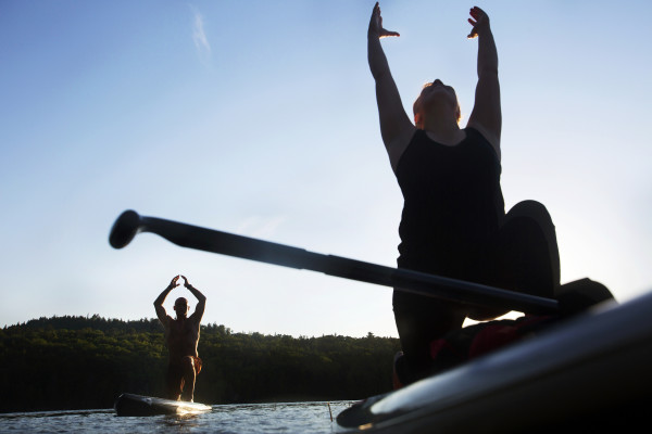Brian Ulbrich (left) of Southwest Harbor and Natalie Feulner do yoga poses during an Acadia Stand Up Paddle Boarding yoga class at Echo Lake on Mount Desert Island.