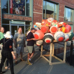 Volunteers prepare to launch a floating sculpture into the Kenduskeag Stream in Bangor on Thursday evening.