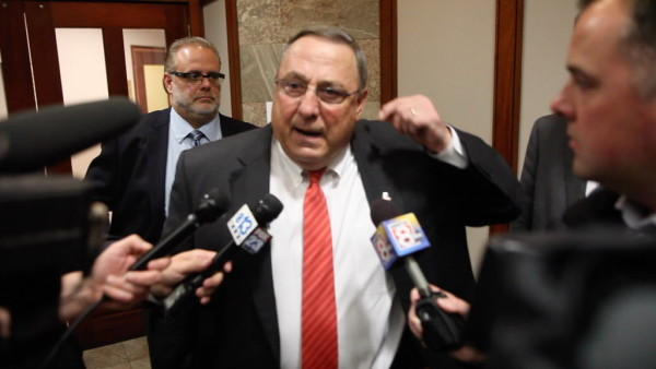 Gov. Paul LePage speaks to reporters outside a press conference in Portland on Wednesday.