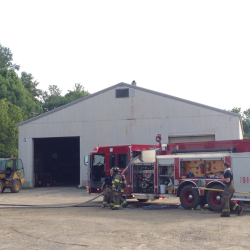 Fire crews respond to burning garage in Hampden