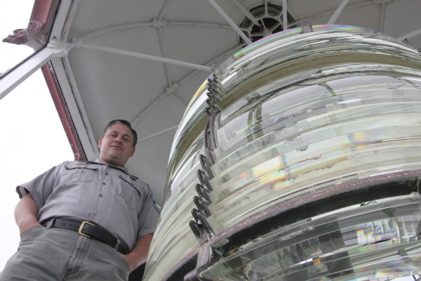 Ranger Shawn Goggin stands at the top of the West Quoddy lighthouse tower, next to the enormous lens that, when lighted, helps guide marine vessels safely along the coast.