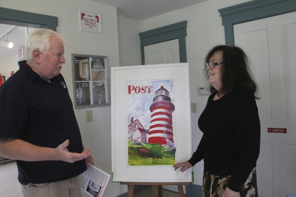 Tim Harrison, editor and publisher of Lighthouse Digest magazine, and Margaret Curley-Clay, chair of the West Quoddy Head Light Keepers' Association, discuss a painting recently donated to the Ron Pesha Lighthouse History Museum at West Quoddy Head Light Station.