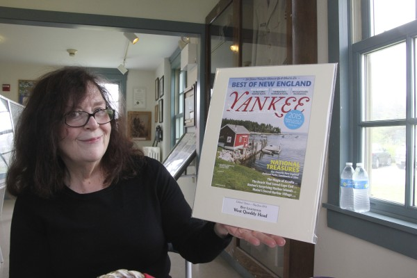 Margaret Curley-Clay, chair of the West Quoddy Head Light Keepers' Association, holds a mounted and matted cover of the May/June edition of Yankee magazine in which the West Quoddy Head Light Station is named the editor's choice as best lighthouse.