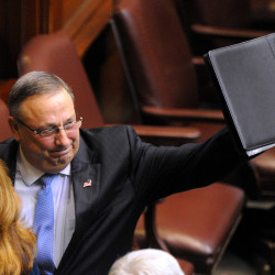 Gov. Paul LePage waves as he leaves the House of Representatives chamber after he delivered his 2014 State of the State address at the State House in Augusta.