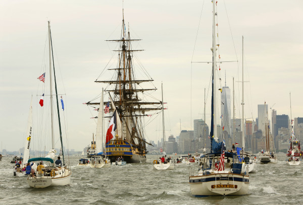 The tall ship L'Hermione leads a parade of ships up the Hudson River, past the Statue of Liberty, to welcome home the L'Hermione and the Spirit of Lafayette back to New York Harbor on Saturday, July 4, 2015, in New York.
