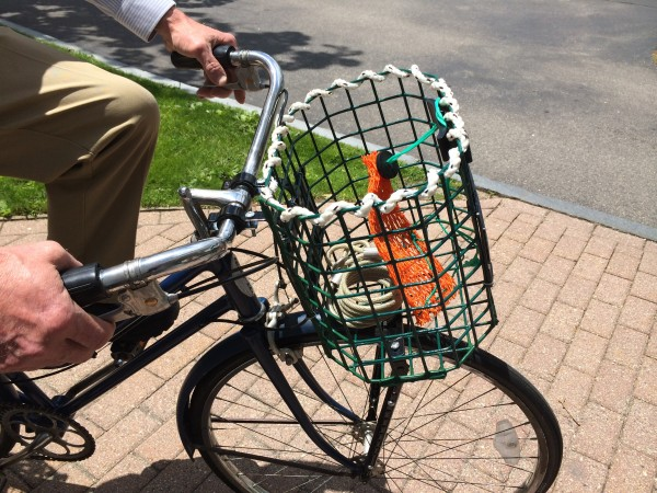 Jim Huebener shows off a Bicycle Trap Basket from Kettle Cove Enterprises on Thursday in Cape Elizabeth. The baskets are available in front- or rear- mounted versions and can be fixed or removable.