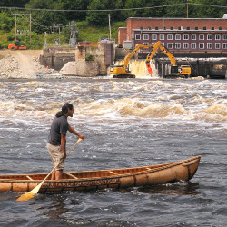 "Joe ""Hugga"" Dana paddles a traditional birch-bark canoe as crews work on the ceremonial breaching of the Veazie Dam on the Penobscot River in this July 22, 2013, file photo."