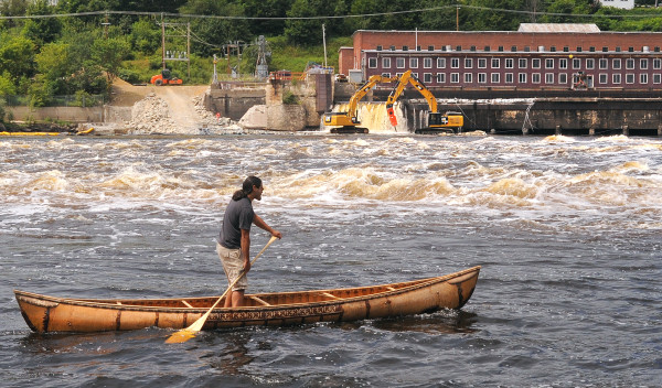 Joe &quotHugga&quot Dana paddles a traditional birch-bark canoe as crews work on the ceremonial breaching of the Veazie Dam on the Penobscot River in this July 22, 2013, file photo.