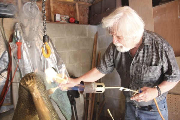 Eastport artist Richard Klyver uses heat to add the patina to a bronze statue of a mermaid that will belong to the city and be unveiled during Bay Day on Aug. 1.