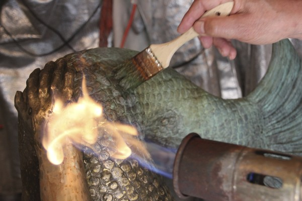 Eastport artist Richard Klyver uses heat to add the patina to his bronze statue of a mermaid that will belong to the city and be unveiled during Bay Day on Aug. 1.