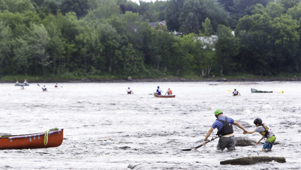 Ryan Linehan helps his son back to their canoe after capsizing in rapids in the Penobscot River on Thursday morning.