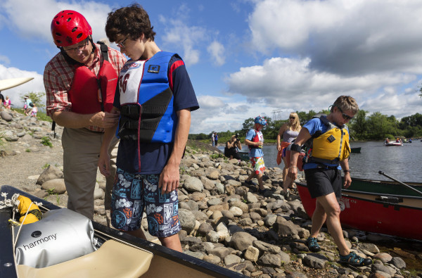 Brian Roth (left) helps Adam Roth, 15, with their bib during the Penobscot River Whitewater Nationals Regatta that started in Old Town and ended in Eddington on Thursday. Races will happen throughout the weekend.