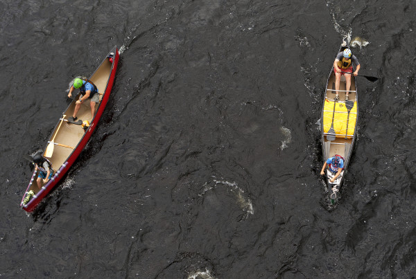 JR Mabee (right boat) and son, Ashton Mabee, 11, make their way down river during the Penobscot River Whitewater Nationals Regatta that started in Old Town and ended in Eddington on Thursday. Races will happen throughout the weekend.
