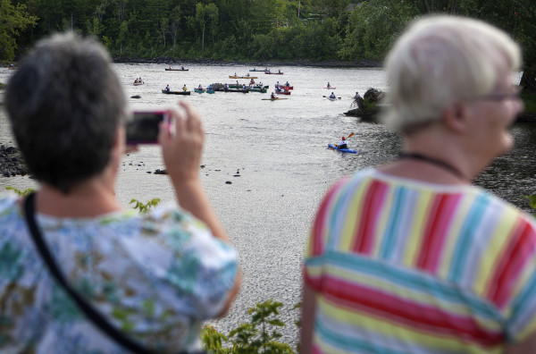 Belinda O'Clair (left) takes photos of the racers with Linda Milbury during the Penobscot River Whitewater Nationals Regatta that started in Old Town and ended in Eddington on Thursday. Races will happen throughout the weekend.