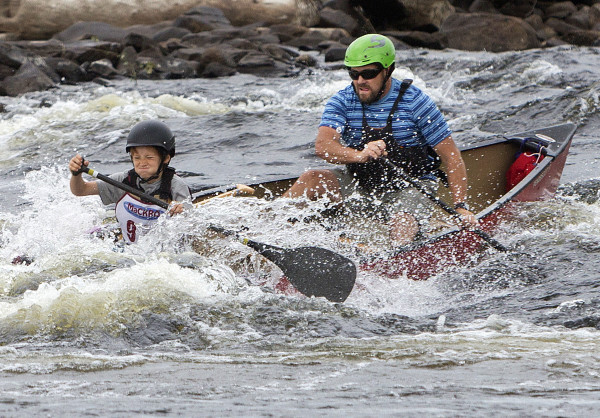 Ryan Linehan and his son, Ryan, dump their canoe during the junior-senior race in the Penobscot River Whitewater Nationals Regatta that started in Old Town and ended in Eddington Thursday.