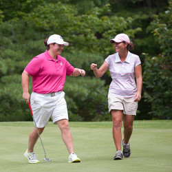 Emily Bouchard (left) and Staci Creech bump fists after sinking their putts on the 12th hole during the Maine Women's Amateur golf tournament Wednesday at the Biddeford-Saco Country Club in Saco.