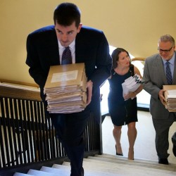 Lance Libby (from left), Adrienne Bennett and Peter Steele of the governor's office carry 65 veto letters up to the Legislature at the State House Thursday morning in Augusta.