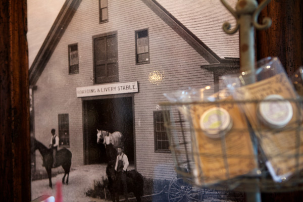 An old photo shows the former life of the big red barn in Cape Porpoise that now houses Farm + Table, purveyors of small-batch household and gift items. Liz and Bruce Andrews opened the shop this spring in the late 19th century building that used to shelter a livery stable.