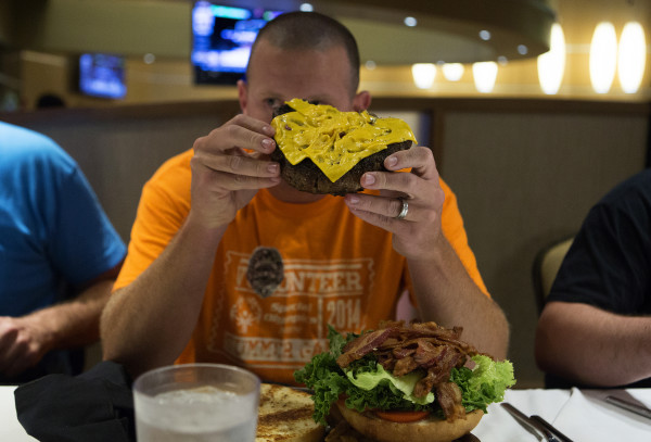 Bangor Detective Tim Shaw chews a bit of the mammoth Paul Bunyan burger during an eating contest Tuesday at the Celebrity Bar and Grill at Hollywood Casino in Bangor on July 8, 2014.