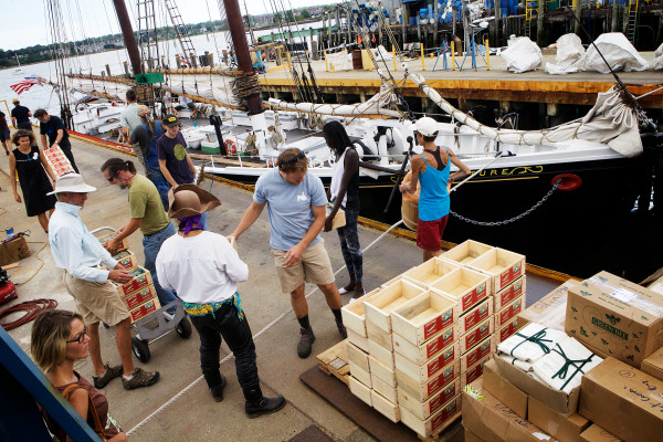 Volunteer stevedores help load Maine agricultural products aboard the schooner Adventure in Portland Thursday. As part of the Maine Sail Freight project, the Adventure will sail for Boston Friday where the products will be sold.