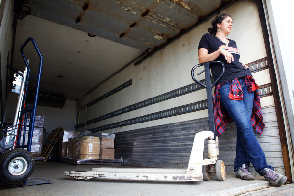 Leah Cook of Crown of Maine Organic Co-op takes a break while unloading a truck in Portland Thursday. As part of the Maine Sail Freight project, the schooner Adventure will sail for Boston Friday, loaded with Maine agricultural products.